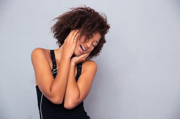 Retrato de uma mulher afro-americana alegre ouvindo música em fones de ouvido na parede cinza