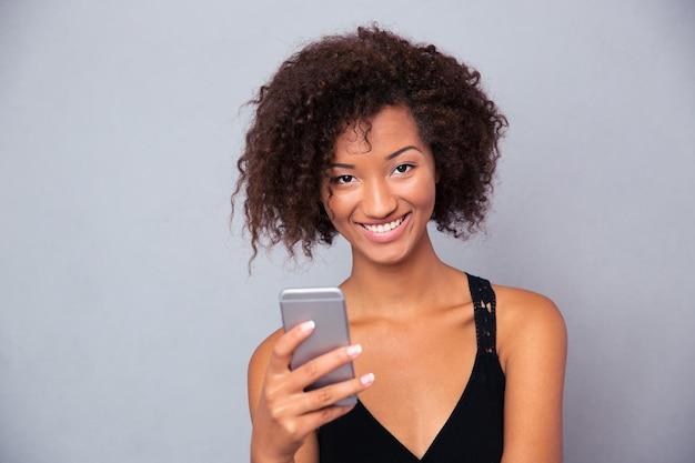 Retrato de uma mulher afro-americana alegre usando o smartphone sobre uma parede cinza e olhando para a frente