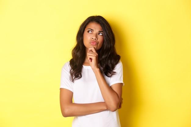 Retrato de uma mulher afro-americana atraente pensando, fazendo sua escolha, olhando para o canto superior esquerdo.