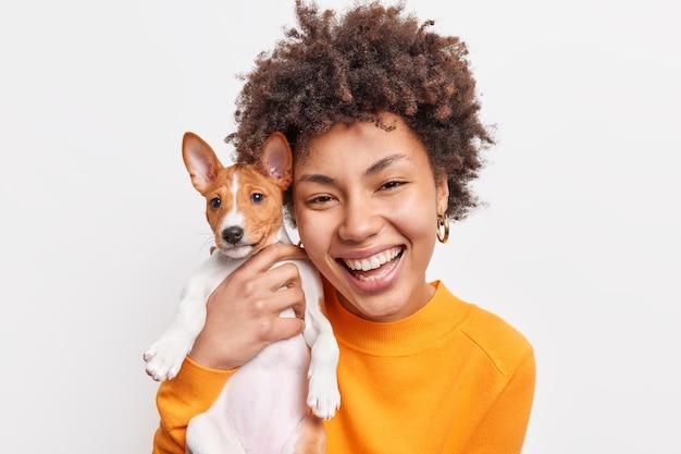 Retrato de uma mulher afro-americana bonita e alegre gosta da companhia de um pequeno cão de raça que usa um jumper laranja e passa o tempo com seu animal de estimação favorito isolado sobre uma parede branca. dono do animal
