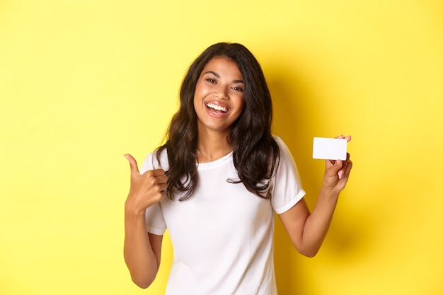 Retrato de uma mulher afro-americana bonita em uma camiseta branca mostrando o polegar para cima e o cartão de crédito