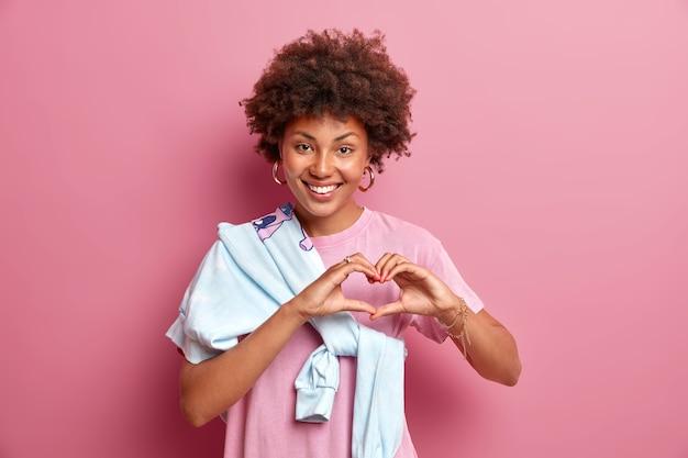 Retrato de uma mulher afro-americana bonita mostra o sinal do coração e sorri, expressa amplamente as emoções românticas, confessa que se preocupa com alguém usa uma camiseta casual com um macacão amarrado no ombro