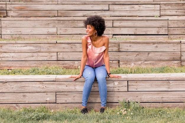 Retrato de uma mulher afro-americana bonita nova feliz que senta-se no assoalho de madeira e no sorriso. primavera ou verão. roupa casual