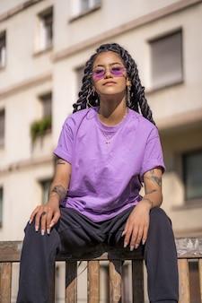 Retrato de uma mulher afro-americana com cabelo comprido, uma camisa roxa e óculos escuros