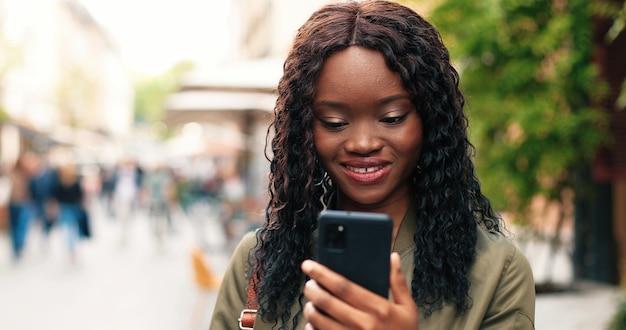 Retrato de uma mulher afro-americana com longos cabelos escuros nas ruas da cidade durante o ...