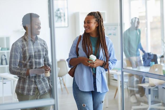 Retrato de uma mulher afro-americana contemporânea saindo do escritório e sorrindo ao passar pela porta de vidro