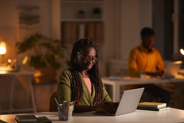Retrato de uma mulher afro-americana contemporânea usando laptop enquanto trabalha até tarde no escritório escuro, copie o espaço