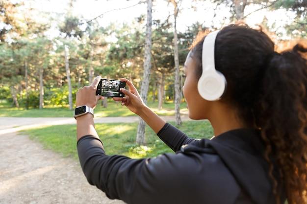 Retrato de uma mulher afro-americana de 20 anos, vestindo um agasalho esportivo preto e fones de ouvido, tirando uma foto de selfie no celular enquanto caminha pelo parque verde