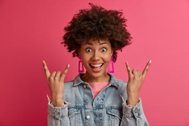Retrato de uma mulher afro-americana emocionada e muito feliz mostra um gesto de rock n roll, gosta de música alta no show, sente felicidade e liberdade, demonstra um sinal de heavy metal se diverte e usa roupas elegantes