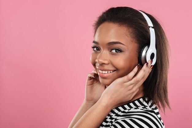 Retrato de uma mulher afro-americana feliz e sorridente em fones de ouvido