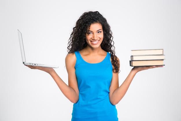 Retrato de uma mulher afro-americana feliz escolhendo entre um laptop ou um livro de papel isolado em uma parede branca.