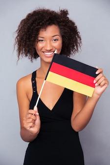 Retrato de uma mulher afro-americana feliz segurando a bandeira da alemanha sobre uma parede cinza e olhando para a frente