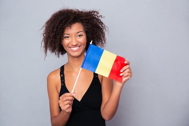 Retrato de uma mulher afro-americana feliz segurando a bandeira da romênia na parede cinza e olhando para a frente