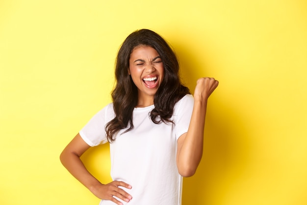 Retrato de uma mulher afro-americana feliz triunfando e vencendo fazendo o punho cerrar e gritando