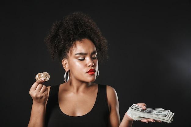 Retrato de uma mulher afro-americana feliz usando maquiagem em pé isolado no espaço negro