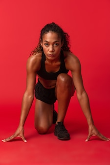 Retrato de uma mulher afro-americana forte em roupa esportiva preta correndo, isolado sobre a parede vermelha