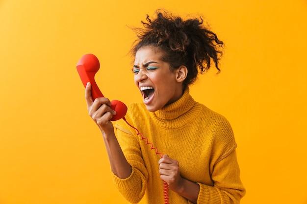Retrato de uma mulher afro-americana nervosa com um penteado afro gritando enquanto fala no aparelho vermelho, isolado