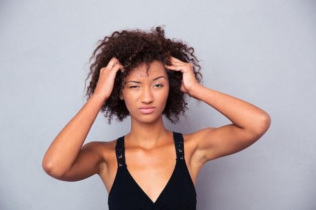 Retrato de uma mulher afro-americana pensativa, olhando para a frente, sobre uma parede cinza