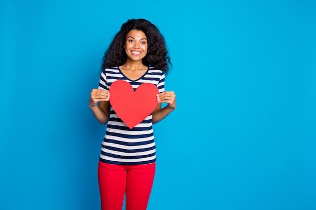 Retrato de uma mulher afro-americana positiva segura um grande coração vermelho de papel cartão