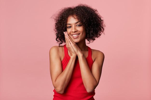 Retrato de uma mulher afro-americana satisfeita com um penteado afro sente prazer, sorri, se regozija, as mãos postas enquanto vai dormir, recebo elogios, flerta, vestindo camiseta vermelha, isolado na parede rosa