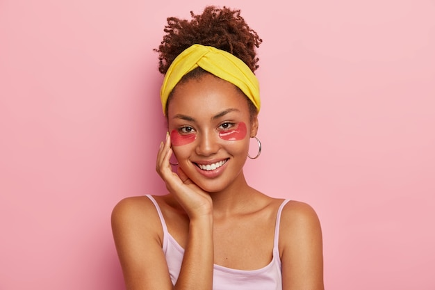 Retrato de uma mulher afro-americana sorridente com tapa-olhos, alivia o inchaço e o inchaço, olheiras, toca a bochecha, penteava o cabelo cacheado em um coque, usa bandana, brincos, sorri agradavelmente