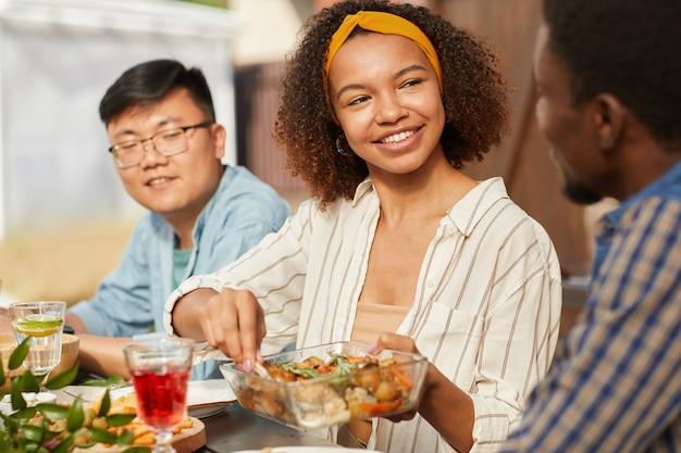 Retrato de uma mulher afro-americana sorridente, compartilhando comida enquanto janta com amigos e família ao ar livre na festa de verão