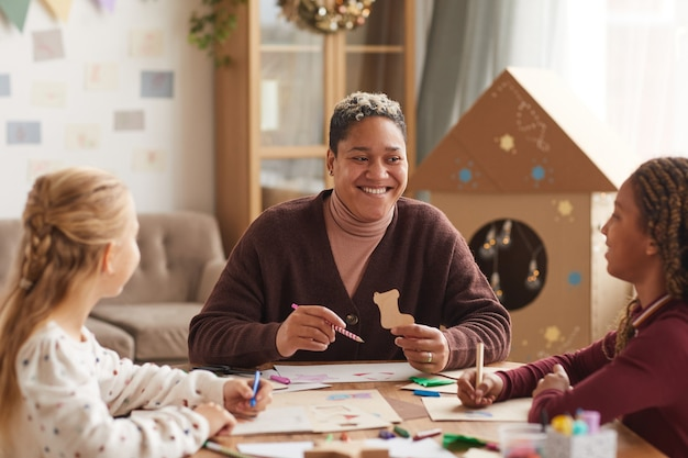 Retrato de uma mulher afro-americana sorridente, dando aula de arte com crianças, aproveitando o desenho na escola