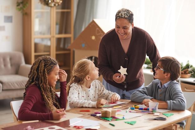 Retrato de uma mulher afro-americana sorridente, dando aula de arte com crianças de várias etnias, fazendo cartões de natal feitos à mão na escola