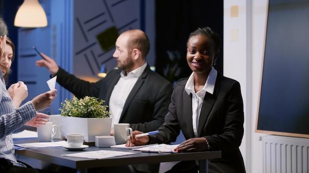 Retrato de uma mulher afro-americana sorridente e focada, sentada à mesa de conferência na sala de reuniões