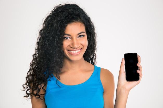 Retrato de uma mulher afro-americana sorridente, mostrando a tela do smartphone em branco, isolada em uma parede branca.