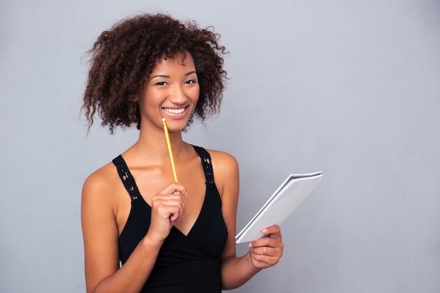 Retrato de uma mulher afro-americana sorridente segurando um caderno com lápis sobre uma parede cinza