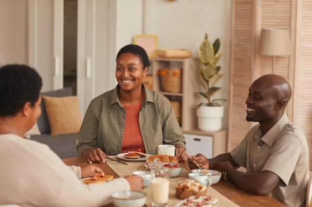 Retrato de uma mulher afro-americana sorridente, sentada à mesa de jantar, enquanto toma o café da manhã com a família em casa