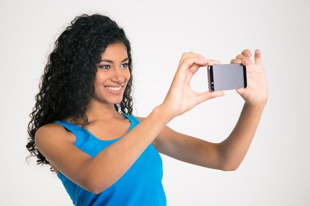 Retrato de uma mulher afro-americana sorridente, tirando foto de selfie em smartphone isolada em uma parede branca.
