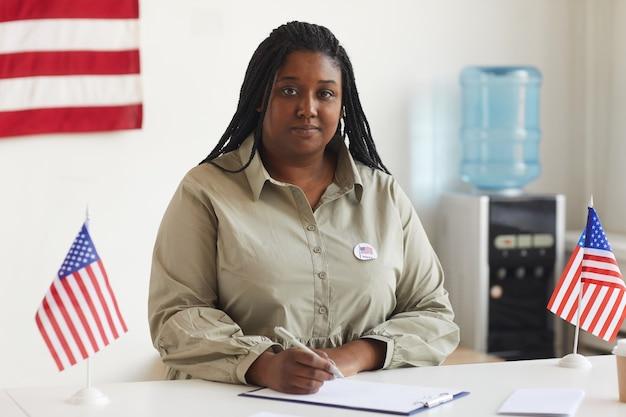 Retrato de uma mulher afro-americana sorridente, trabalhando em uma seção eleitoral no dia das eleições e registrando eleitores, copie o espaço