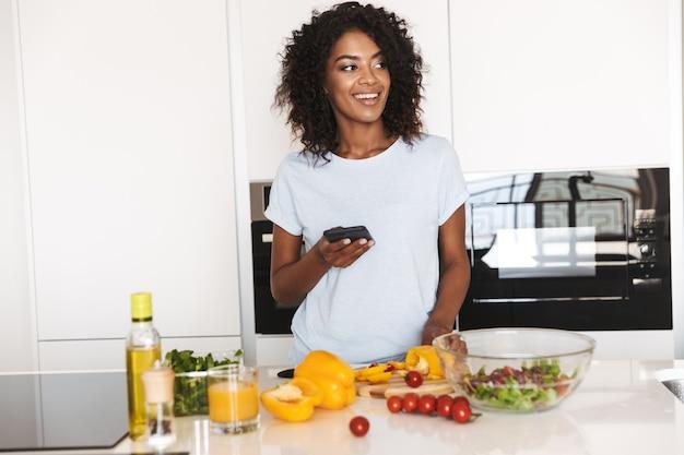 Retrato de uma mulher afro-americana sorridente usando telefone celular