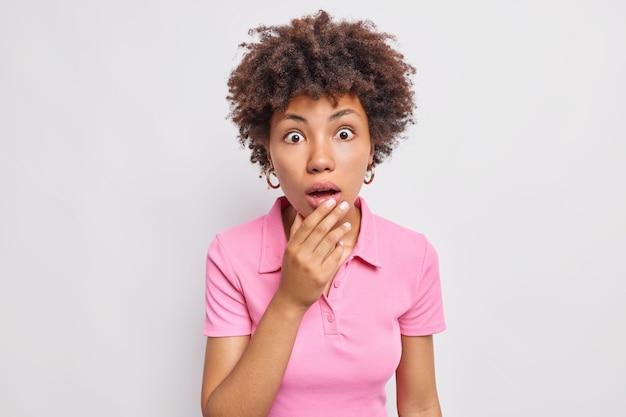 Retrato de uma mulher afro-americana surpresa que fica boquiaberta de admiração e olha sem palavras de espanto e descrença, não consegue acreditar que seus olhos vestem uma camiseta casual isolada sobre uma parede branca