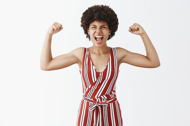 Retrato de uma mulher afro-americana triunfante, alegre e expressiva, bonita, de macacão listrado estiloso, levantando os braços para mostrar os músculos que gritam de alegria e olhando para cima