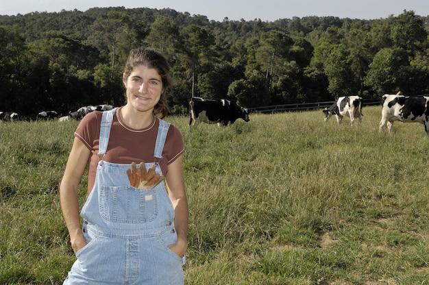 Retrato de uma mulher agricultora com algumas vacas