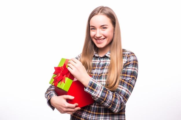 Retrato de uma mulher alegre abrindo uma caixa de presente isolada em uma parede branca