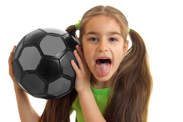 Retrato de uma mulher alegre com uma bola de futebol mostra tonque isolado no branco