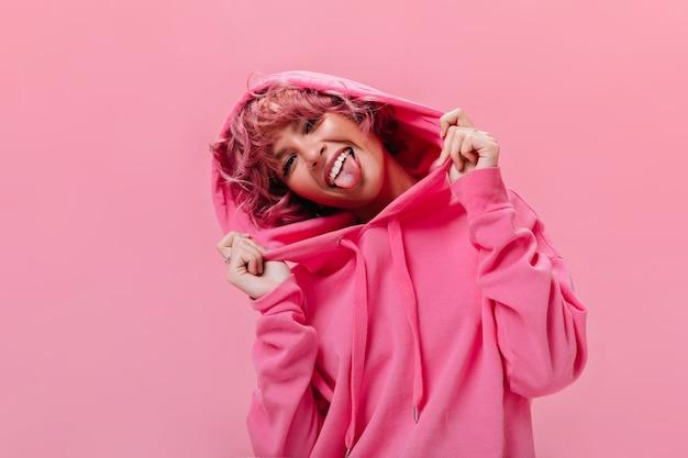 Retrato de uma mulher alegre e ativa de cabelo rosa com um capuz fúcsia enorme mostra a língua e faz uma careta na parede isolada