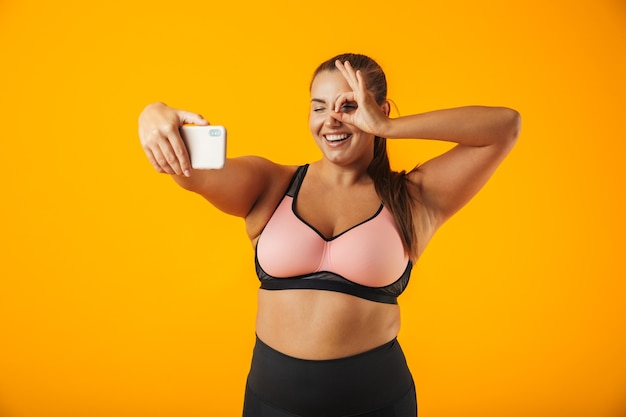 Retrato de uma mulher alegre e com excesso de peso, vestindo roupas esportivas, em pé isolado na parede amarela, tirando uma selfie com o celular