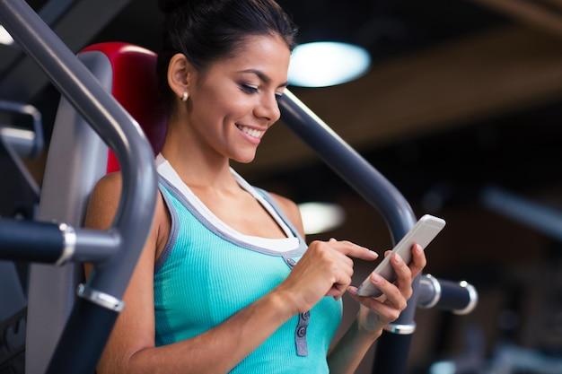 Retrato de uma mulher alegre e esportiva usando smartphone no ginásio de fitness