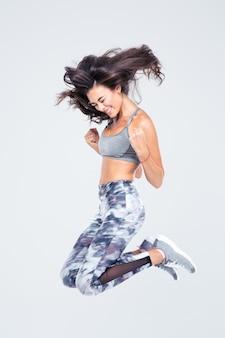 Retrato de uma mulher alegre e fitness pulando isolado em uma parede branca