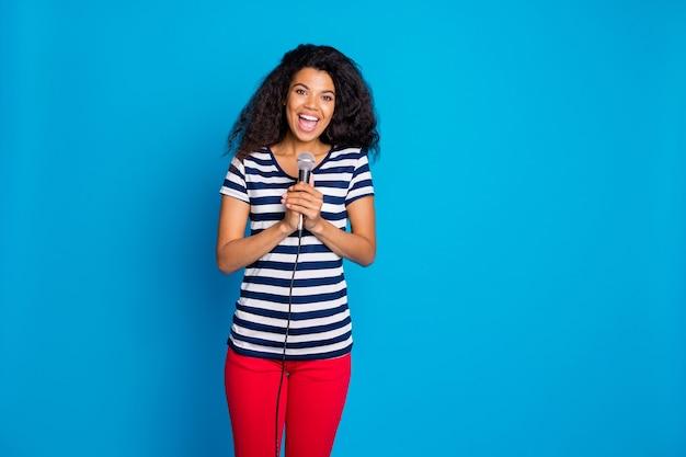 Retrato de uma mulher alegre e positiva segurando o microfone no palco e cantar