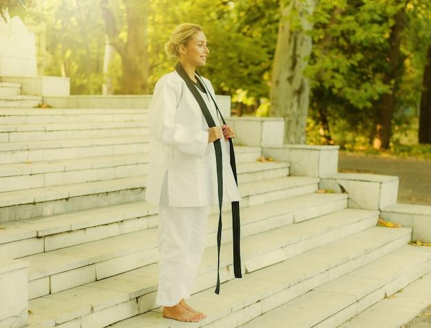 Retrato de uma mulher alegre lutadora em quimonos brancos e faixa preta ao ar livre