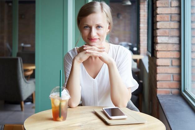 Retrato de uma mulher alegre, olhando para a câmera e sorrindo para a mesa de café
