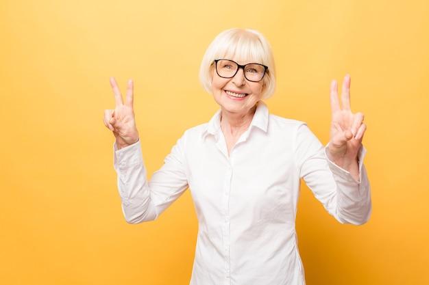 Retrato de uma mulher alegre sênior gesticulando vitória isolada sobre fundo amarelo.