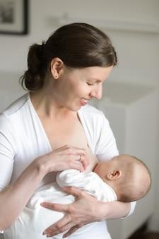 Retrato de uma mulher amamentando uma criança, nas mãos dela