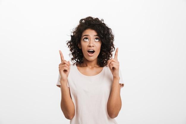Retrato de uma mulher americana em t-shirt básica com cabelo encaracolado, olhando para cima e apontando o dedo indicador na copyspace, isolado sobre a parede branca